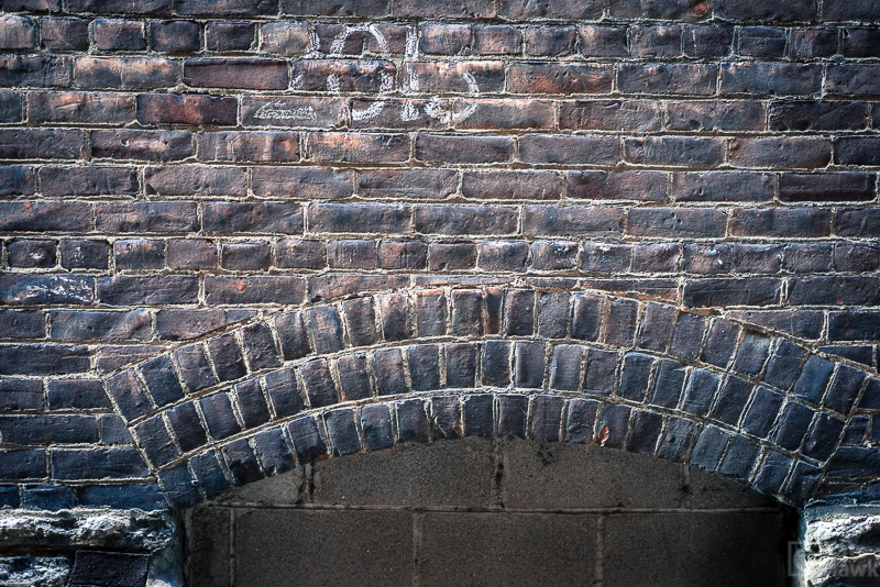 The side of a brick building with some numbers written on it.
