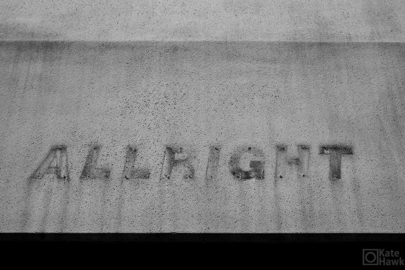 The letters ALLRIGHT stained on concrete
